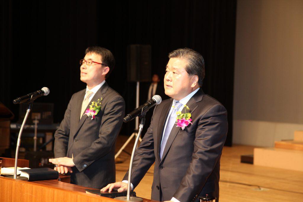 4通訳をする黄萬龍牧師と講師を紹介する志垣担任牧師
